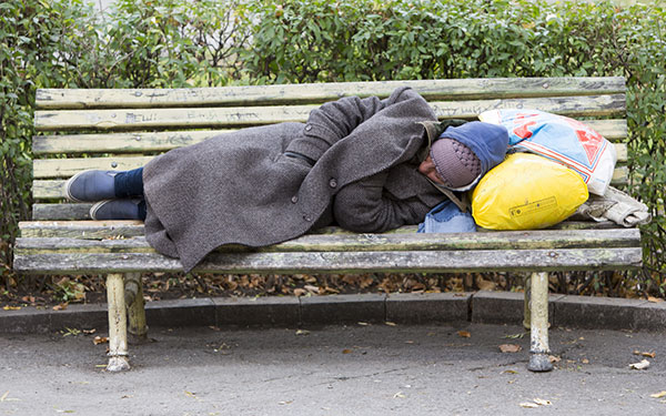 Photo of a man sleeping rough on a bench