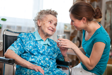 Photo of friendly care worker helping an elderly lady