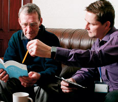 Two men discussing a form