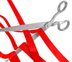 Scissors cutting red tape