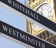 Close up of Big Ben clockface with signs for Whitehall and Westminster