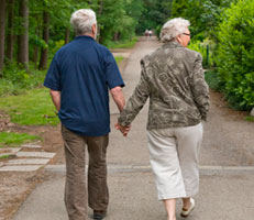Two pensioners walking hand in hand