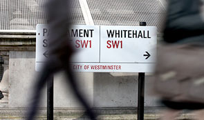 Blurred image of person walking past Parliament road sign