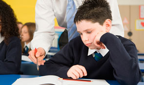Pupil with teacher leaning over his shoulder
