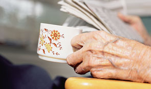 Elderly hand holding a cup