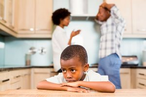 Child with arguing parents in background