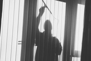 silhouette of man cleaning a window