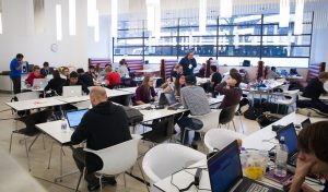 People working at laptops in the NAO canteen