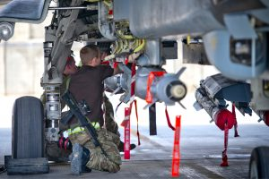 Engineer beneath the undercarriage of a military plane