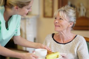Carer serving meal to patient