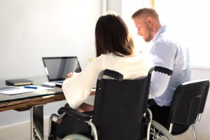 Woman in a wheelchair in discussion in an office environment
