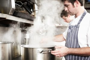 Chef with a steaming saucepan