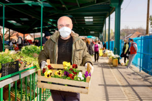 Man in a market holding a crate of flowers