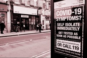 Sign on shopping street with information about COVID-19